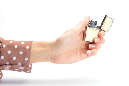 cigarette lighter: Businesswomans hand holding cigarette lighter with flame