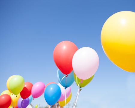 Volare palloncini colorati contro il cielo blu