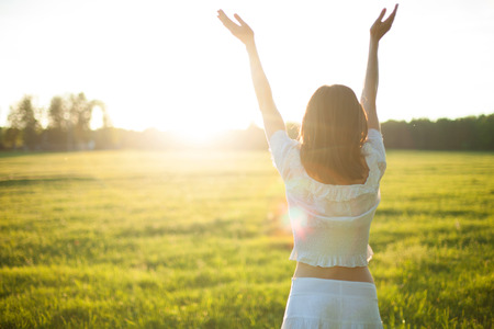 Young woman enjoying sunlight with raised arms in straw field Standard-Bild