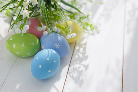 Colorful decorated easter eggs on white wood background. Happy Easter. photo