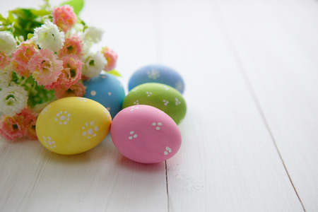 white wood: Colorful decorated easter eggs on white wood background. Happy Easter. Stock Photo