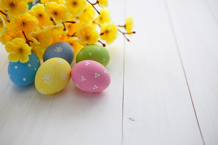Colorful decorated easter eggs on white wood background photo