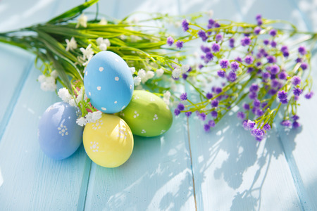 easter flowers: Colorful decorated easter eggs on white wood background Stock Photo