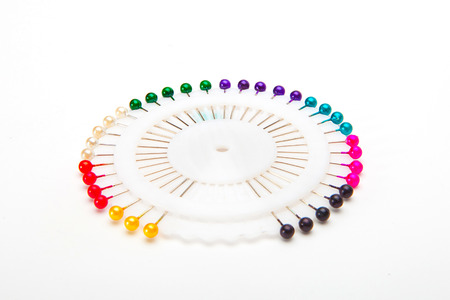 colorful safety pins lying on a white background photo