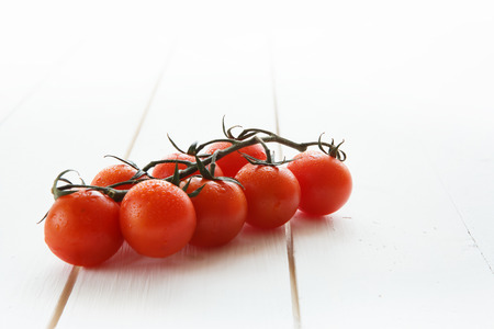 palate: Delicious red tomatoes cherry on a white wood table background. Stock Photo