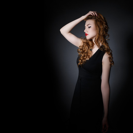 Beautiful  Woman on the Dark Background of Dark Wall photo