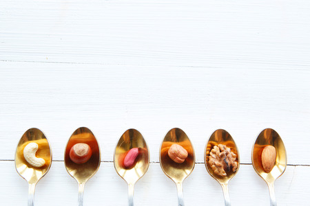 Nuts in Löffel auf weißem Holztisch Standard-Bild - 39516905