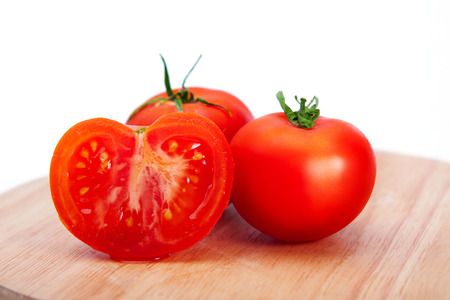 mouthwatering: Two mouth-watering delicious whole tomato and a half on a cutting board on a white background. Tomato Stock Photo