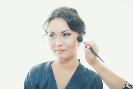 Stylist pinning up a brides hairstyle photo