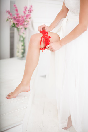 garter belt: Young Bride Putting On Red Grater Stock Photo