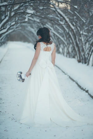 winter wedding: Beautiful bride with a bouquet standing in a snowy winter park at the beautiful snow-covered trees