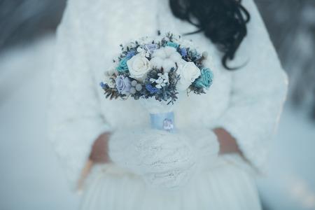 婚禮: 冬季婚禮花束。新娘在美麗的冬天手套舉行婚禮花束的冬天。 版權商用圖片