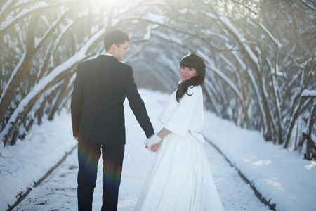 couple winter: Wedding in the winter. The newlyweds are in the winter park and looking at each other. Stock Photo