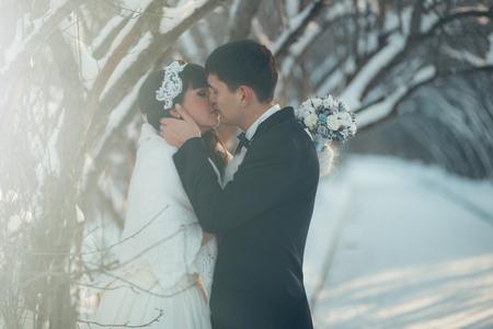 marido y mujer: Boda en el invierno. Los reci�n casados ??se encuentran en el parque de invierno y mirando el uno al otro. Foto de archivo
