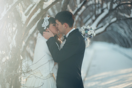 ślub: Wedding in the winter. The newlyweds are in the winter park and looking at each other. Zdjęcie Seryjne