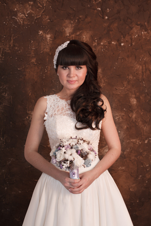 aciculum: Bride on a dark wall background. The bride is smiling and looking at the camera. Stock Photo