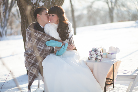 adult couple: Bride and groom at a picnic in a winter park.