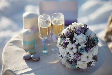 coloured background: Winter wedding bouquet. Wedding bouquet of flowers lying on a chair near two wedding glasses and candle. Stock Photo