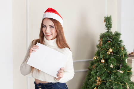 mrs  santa claus: Woman with Christmas hat holding blank banner