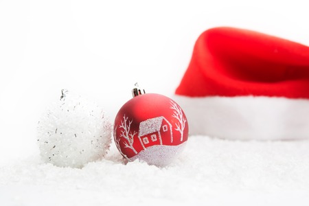 christmas hats: Santa hat with red Christmas decoration and two red matt christmas balls on white background.