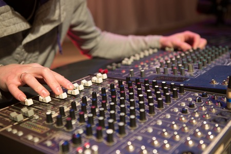 adjusting: Professional audio mixing console with faders and adjusting knobs Stock Photo