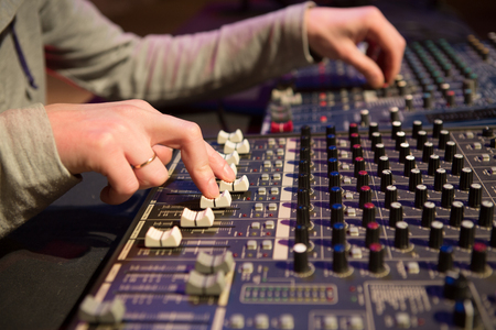 Professional audio mixing console with faders and adjusting knobs Stock Photo