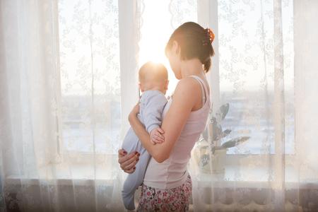 Liebevolle Mutter spielt mit ihrem Baby auf einem Fenster mit Sonnenaufgang Hintergrund sitzt Standard-Bild - 51067789