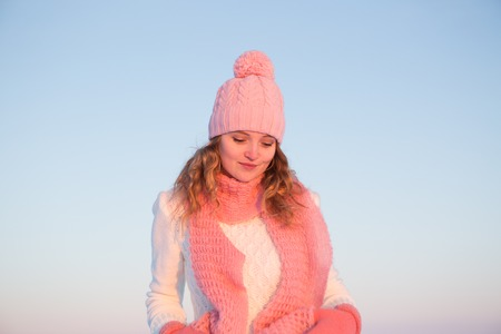 french model: Emotive portrait of a fashionable model in white coat and beret standing at the winter seaside. Sunny weather. French style. Outdoor shot. Stock Photo