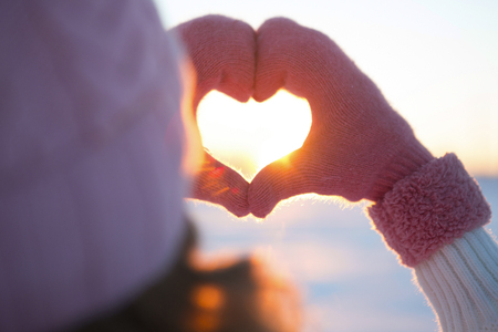 Žena ruce v zimě rukavice symbol srdce ve tvaru životní styl a pocity koncepce s západu slunce světlo přírodě na pozadí v zimě Reklamní fotografie