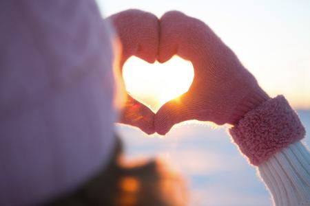 Frau, die Hände im Winter Handschuhe Herzsymbol geformt Lifestyle und Emotionen Konzept mit Sonnenuntergang Licht der Natur auf Winter Hintergrund