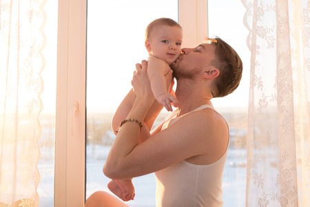 6 12 months: Young father playing and kissing with baby son near the window