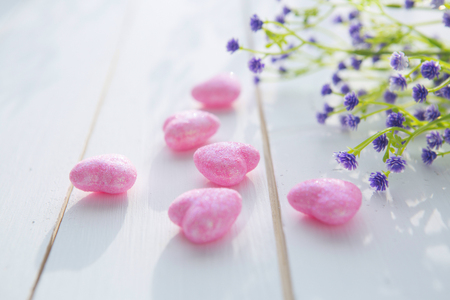 out of engagement: Pink hearts and a bouquet of wildflowers on wooden board, Valentines Day background Stock Photo