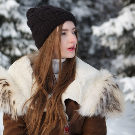 Young woman in winter. Winter woman in snow looking up on snowing cold winter day.