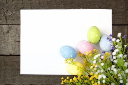 osterei: Ostereier und leere Notiz auf Holzuntergrund. Frohe Ostern.