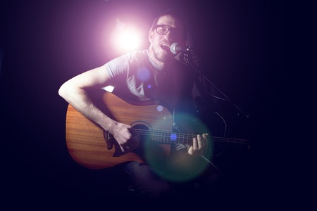 Musician playing acoustic guitar and singing on dark background