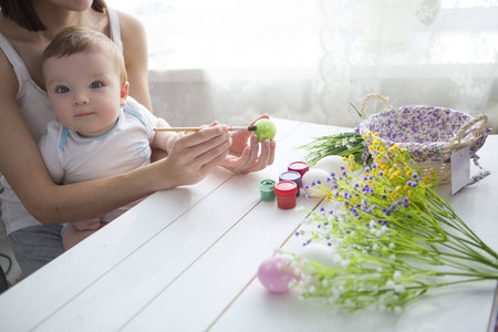 toddler: Little toddler boy and his mother decorating Easter egg, traditional action for Eastern holiday, at home