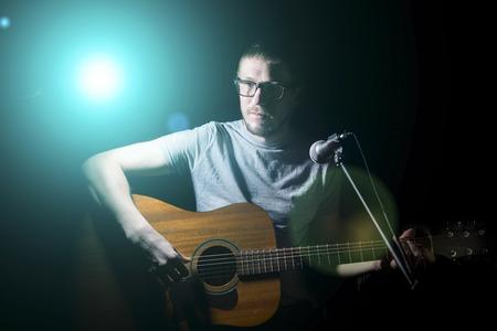 musico: Músico que toca la guitarra acústica y cantando sobre un fondo oscuro