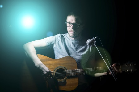 young musician: Musician playing acoustic guitar and singing on dark background