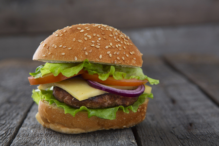 pomme: Delicious hamburger  with fresh vegetables on wooden table.