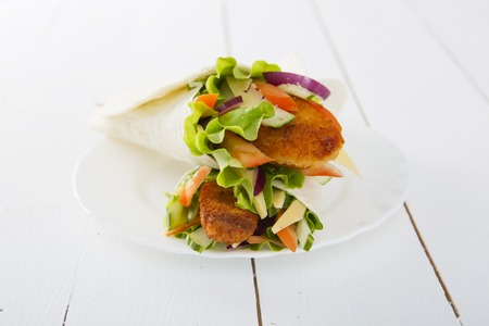 spring rolls with vegetables and chicken in plat on wooden table