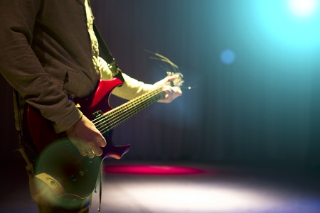 hand jamming: Man staying on stage and playing electric guitar on black dark background. Stock Photo