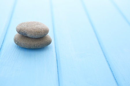 planar: Zen stones wooden table. Pile planar stones on the old blue wooden rustic table. Stock Photo