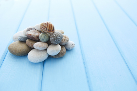 smooth stones: Pile of clean white smooth stones on a blue smooth wooden table
