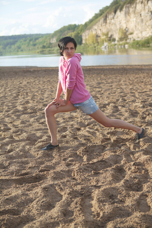 sportswoman: young beautiful sportswoman doing exercises on beach Stock Photo