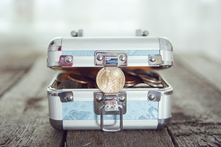 putting money in pocket: Box for savings full of coins on wooden table. Cross Processing tone colored. Stock Photo