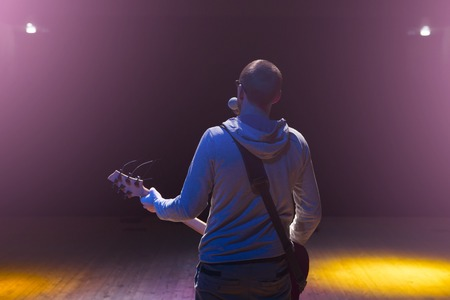 staying: Man staying on stage and playing electric guitar on black dark background. Stock Photo