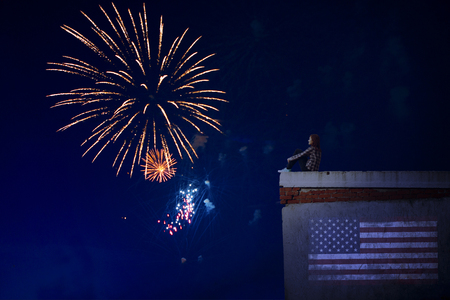 american flag fireworks: Woman sitting on the roof against the backdrop of beautiful fireworks. Independence Day or Fourth of July, 4th of July.
