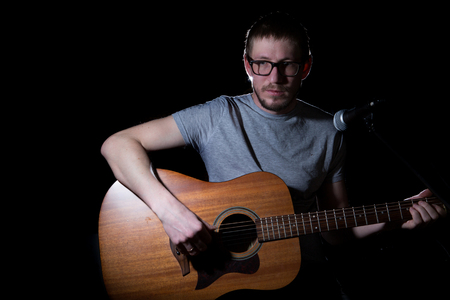 band bar: Musician playing acoustic guitar and singing on dark background