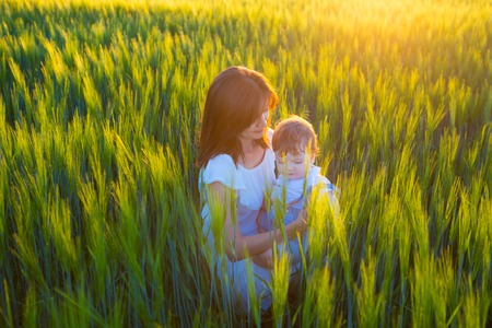 belonging to the caucasoid race: Beautiful woman with a baby in a field of wheat