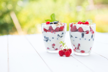 Natural yogurt with fresh raspberries, black currant and muesli. . Healthy dessert. Healthy food concept. Stock Photo